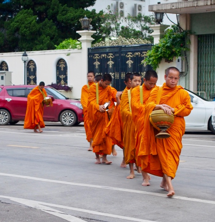 A group of monks coming for alms early in the morning in Nan, Thailand
